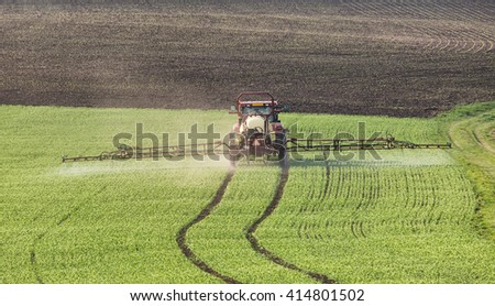 Tractor pours fertilizer in agriculture field - stock photo