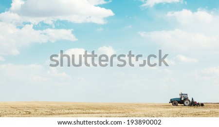 Tractor seeding a field on the prairies  - stock photo