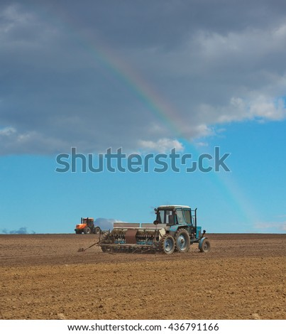 Tractor sowing the field with the seeder and a rainbow in the sky - stock photo