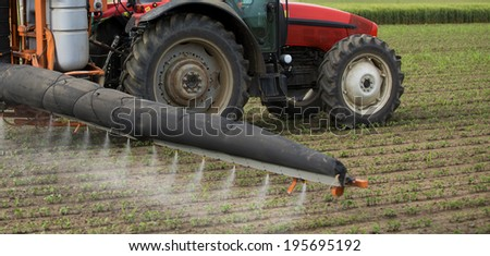 Tractor spraying crops field - stock photo