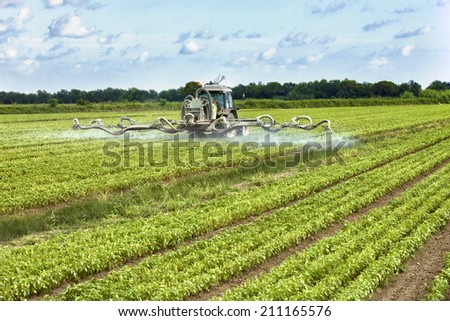 tractor spraying pesticides on a field - stock photo