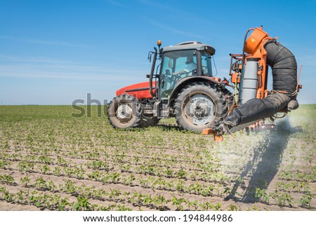 tractor spraying pesticides on soy bean - stock photo