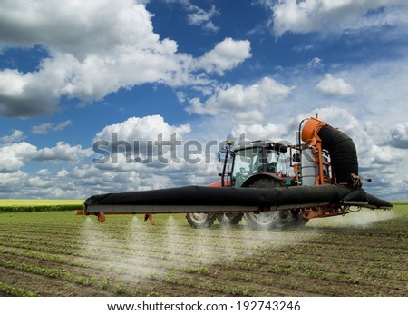 Tractor spraying soybean field at spring over amazing cloudscape - stock photo