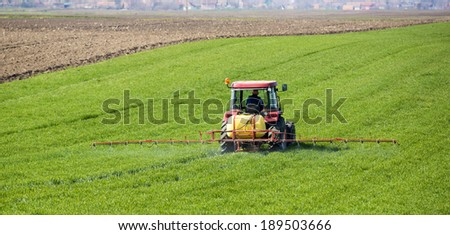 Tractor spraying wheat field with sprayer, herbicides and pesticides - stock photo