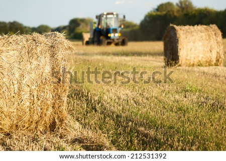 Tractor throwing out hay roll - stock photo