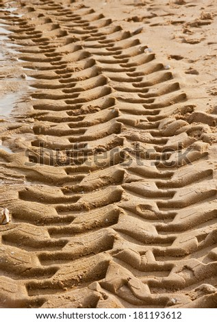 Tractor tire tracks on beach sand - stock photo