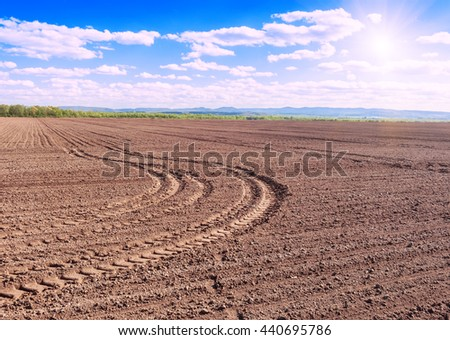 tractor tracks on freshly plowed field under blue sky - stock photo