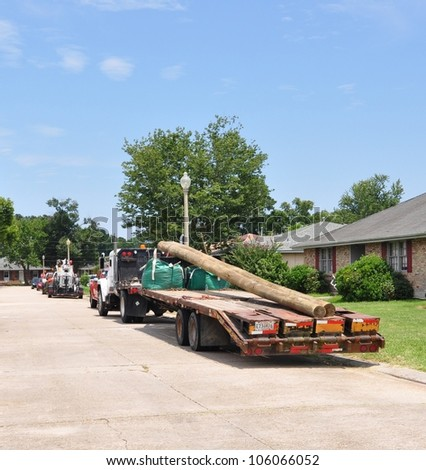 Tractor Trailer Truck Delivering New Telephone Poles - stock photo