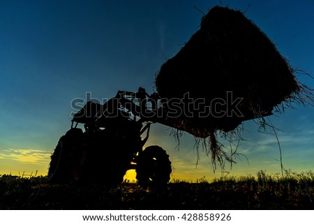 tractor up-lift in silhouette during sunset - stock photo
