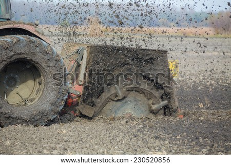 Tractor with double wheeled ditcher digging drainage canal - stock photo