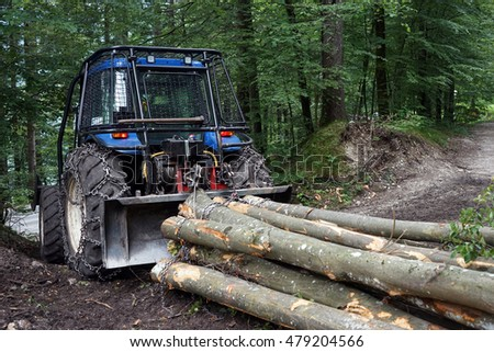 Tractor with logs on the dirt road in forest, Slovenia