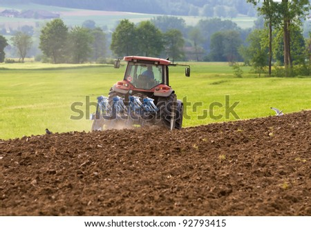tractor with plough ploughing a grass covered field, concept for agriculture business - stock photo