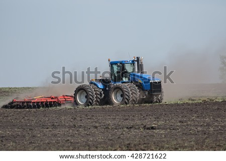 tractor with plow plowing a field - stock photo