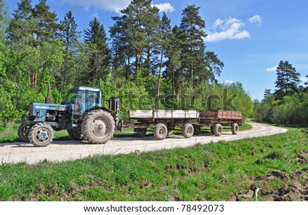 Tractor with trailer, country road in the forest, spring sunny day