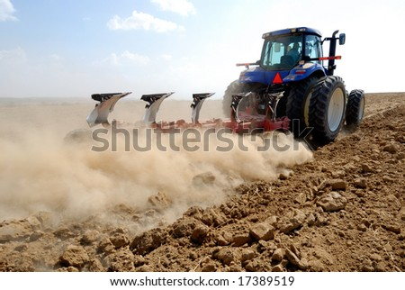 tractor working at field - stock photo