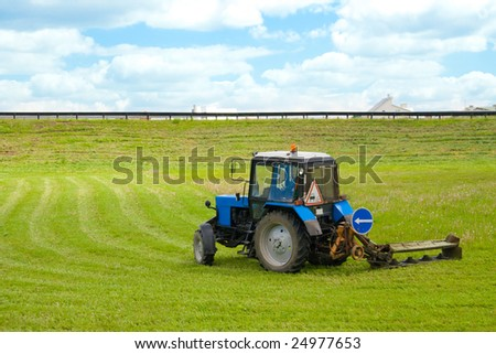 tractor, working on cutting grass in rural areas