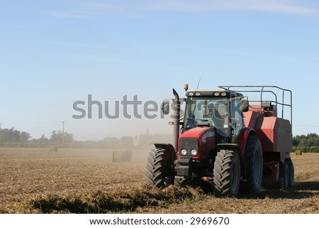 Tractor working to bail pea straw on the Canterbury Plains, New Zealand