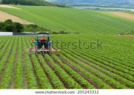 Tractors in the fields. - stock photo