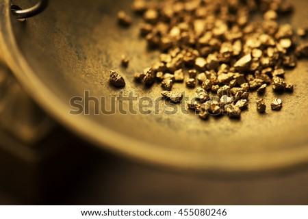 Trade and exchange. Weighing a gold nugget on a old brass scale dish.for trading. Shallow depth of filed. - stock photo