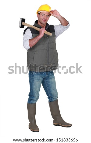Tradesman carrying a mallet and wearing a hard hat and rubber boots - stock photo