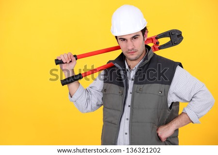 Tradesman carrying a pair of large clippers on his shoulder - stock photo
