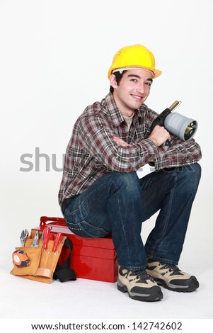 Tradesman holding a blowtorch and sitting on his toolbox - stock photo