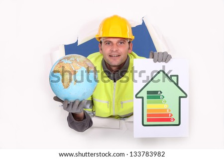 Tradesman holding a globe and an energy efficiency rating chart - stock photo