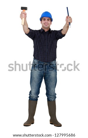 Tradesman holding a hammer and chisel - stock photo