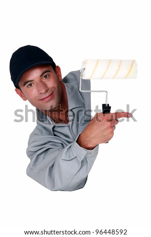 Tradesman holding a paint roller and pointing to a blank sign - stock photo