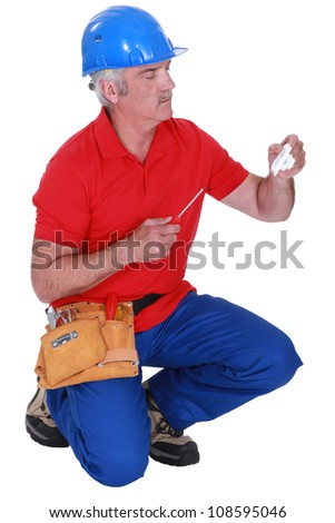 Tradesman holding a plug and a screwdriver - stock photo