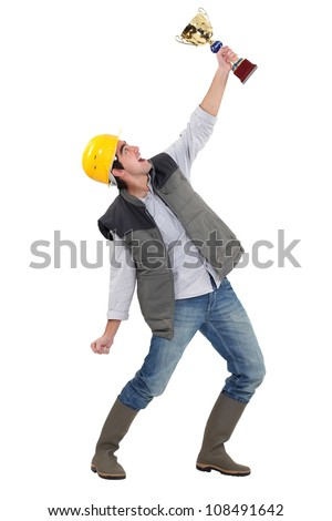 Tradesman holding a trophy - stock photo