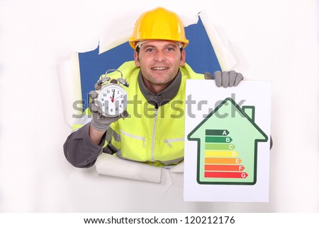 Tradesman holding an energy efficiency rating chart and an alarm clock - stock photo