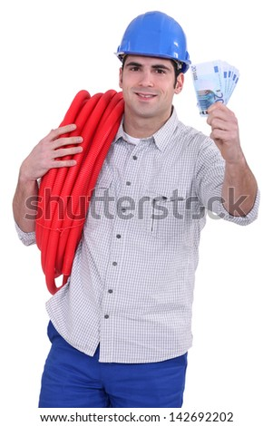 Tradesman holding money and corrugated tubing around his shoulder - stock photo