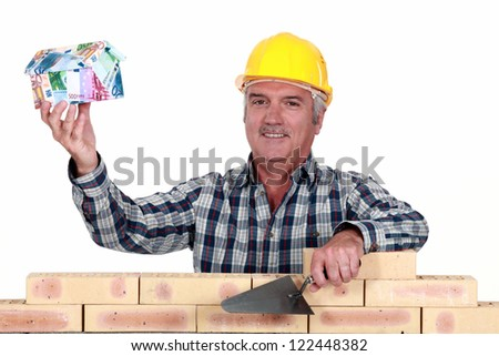 Tradesman holding up a house model make out of money - stock photo