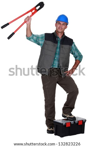 Tradesman holding up a pair of large clippers - stock photo