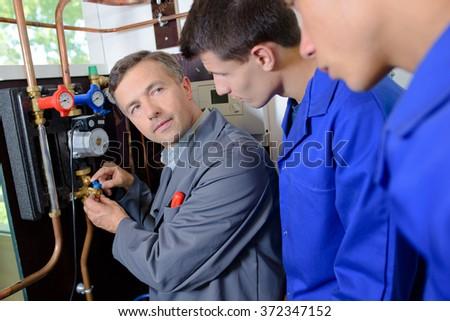 Tradesman training two apprentices - stock photo