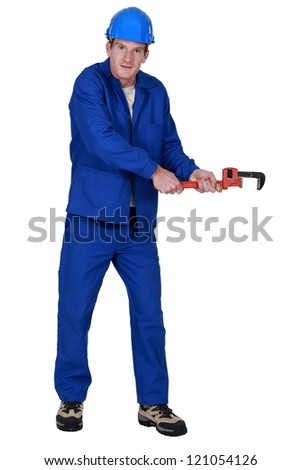 Tradesman trying to pull an invisible object using a pipe wrench