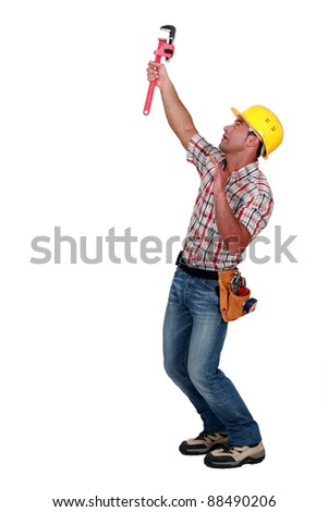 Tradesman using a pipe wrench to tighten an object - stock photo