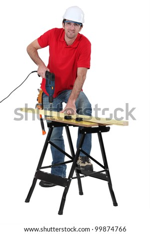 Tradesman using a power tool - stock photo