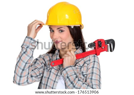 Tradeswoman holding  pipe wrench - stock photo
