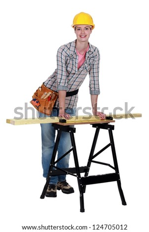 Tradeswoman leaning against a workbench - stock photo