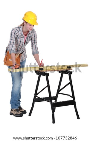 Tradeswoman measuring a plank of wood - stock photo