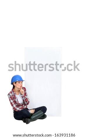 Tradeswoman sitting cross-legged - stock photo