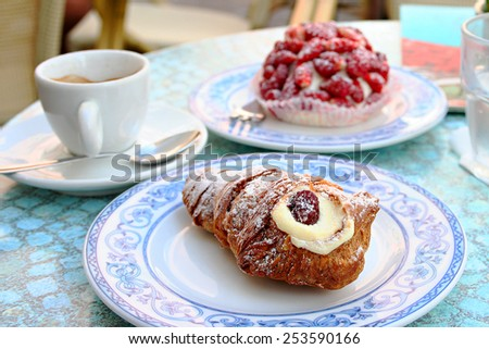 Tradition cake of region Campania Code di Aragosta on white blue plate with cup of coffee and strawbarry cake background in Sant Angelo, Ischia - stock photo