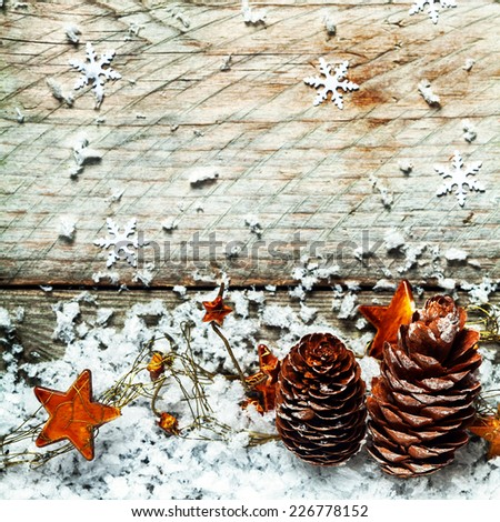 Traditional Advent or Christmas background with dried pine cones and golden orange stars in a bed of winter snow against old wooden boards decorated with snowflakes, square format - stock photo