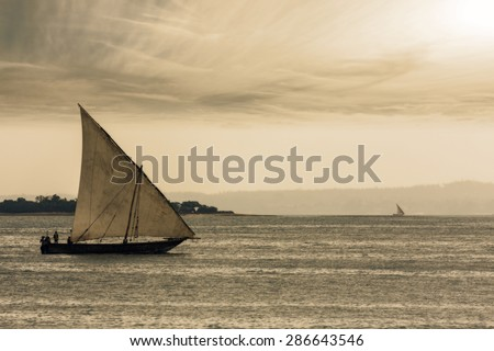 traditional african dhow sailing vessel with full sail to the wind with warm evening autumn color - stock photo