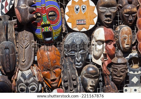 Traditional african masks hanging for sell in a market stall  - stock photo