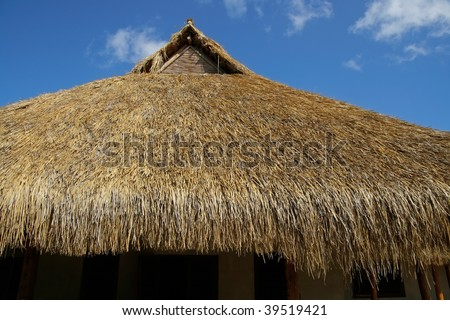 Traditional African thatched roof against a blue sky with clouds