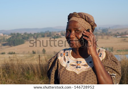 Traditional African Zulu woman speaking on mobile cell phone telephone in rural KwaZulu-Natal. - stock photo
