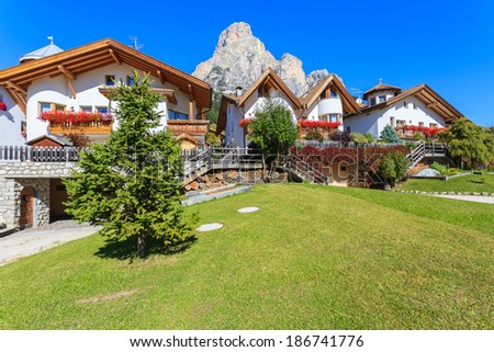 Traditional alpine houses decorated with flowers on sunny summer day, La Villa village, Dolomites Mountains, Italy - stock photo